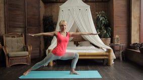 Signora di forma fisica esegue i asanas di yoga in camera da letto a casa video d archivio
