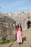 Signora di hippy che cammina in un castello inglese rovinato un giorno soleggiato fotografie stock