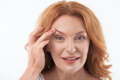 Signora di mezza età allegra soddisfatta con il trattamento dello skincare Fotografia Stock