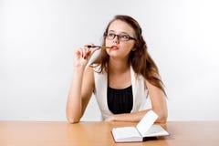 Signora di pensiero di affari in vetri che si siedono al suo scrittorio Immagini Stock