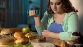Signora di peso eccessivo che esercita e che esamina tristemente alimenti industriali, problema di obesità fotografia stock