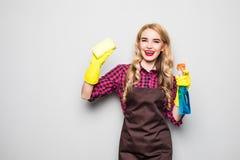 Signora di pulizia Pulizia della donna che sfrega e che raggiunge di lucidatura e che allunga con il panno di pulizia e la bottig Immagine Stock