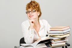 Signora di Redhead che si siede allo scrittorio con la pila di libri Immagini Stock