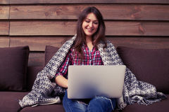 Signora di rilassamento che scrive sul computer portatile mentre sedendosi sul sofà Fotografia Stock Libera da Diritti