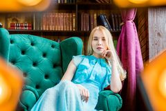 Signora elegante che porta vestito blu che si siede nella sedia nella biblioteca Bellezza, modo Immagini Stock