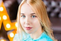 Signora elegante che porta vestito blu che si siede nello studio del sottotetto con la stella dietro Bellezza, modo Fotografia Stock Libera da Diritti