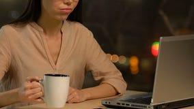 Signora esaurita sovraccarica che lavora al computer portatile ed al tè bevente, non avendo idee stock footage