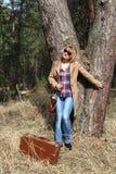 Signora-fotografo con la vecchia valigia dell'annata e della macchina fotografica sotto il grande pino Fotografie Stock