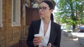 Signora frustrata di affari utilizza il telefono cellulare mentre cammina intorno alle vie della città con caffè archivi video