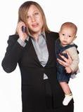 Signora frustrata sul telefono con il bambino Fotografia Stock