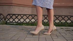 Signora in gambe del vestito in tacchi alti beige cammina lungo la via video d archivio