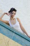 Signora graziosa che si appoggia una parete, capelli riuniti guarda insieme Fotografie Stock Libere da Diritti