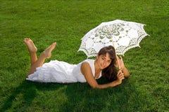 Signora graziosa che si distende sull'erba Immagini Stock