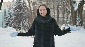 Signora graziosa getta la neve vicino a se stessa nel parco dell'inverno stock footage