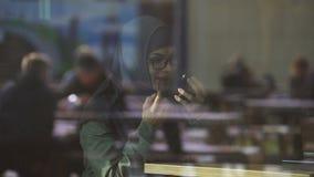 Signora graziosa nel hijab che applica rossetto in caffè, sorridente in specchio, civetta video d archivio