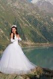 Signora graziosa in un vestito da cerimonia nuziale in montagna immagini stock libere da diritti