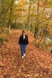 Signora Hiking An Autumn Trail Immagine Stock