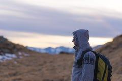 Signora incappucciata con lo zaino che riposa sulle alpi al tramonto Immagine Stock Libera da Diritti