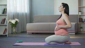 Signora incinta che fa gli esercizi di rilassamento e di respirazione, preparanti per il parto video d archivio
