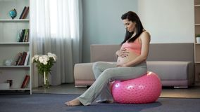 Signora incinta dei giovani che ascolta suo battersi dei babys, sedentesi sulla palla di forma fisica fotografia stock