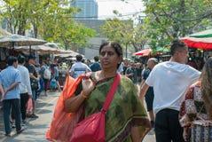 Signora indiana sta portando il sacchetto di plastica che cerca le cose per comprare immagini stock