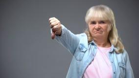 Signora invecchiata infelice che mostra gesto dei pollici-giù, insoddisfatto del governo statale fotografie stock libere da diritti