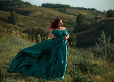 Signora lussuosa in vestito da verde lungo con le spalle nude fotografia stock libera da diritti
