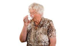 Signora maggiore con un vetro di acqua Fotografia Stock Libera da Diritti
