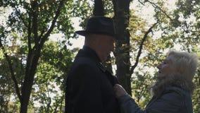 Signora matura che abbottona un cappotto al suo marito al parco archivi video