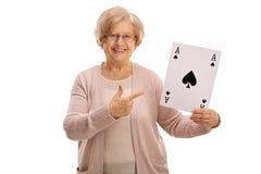 Signora matura che tiene una carta ed indicare dell'asso di picche Fotografia Stock
