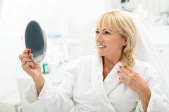 Signora matura felice è soddisfatta con il trattamento dello skincare Immagini Stock