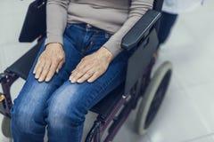 Signora matura sta sedendosi la sedia a rotelle in ospedale fotografia stock