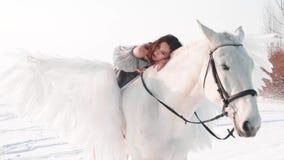 Signora mora graziosa incantante in un vestito d'annata grigio lungo con le spalle nude si siede a cavallo del cavallo, tenero si archivi video
