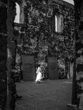 Signora nel bianco cammina attraverso la chiesa abbandonata con le pietre tombali Fotografia Stock