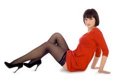 Signora nel bianco isolato seduta rossa del vestito Fotografia Stock