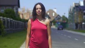 Signora nella venuta rossa del vestito più vicina sulla via aperta, bella donna cammina verso stock footage