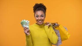 Signora nera allegra che tiene mazzo di euro e di sacchetti della spesa, vendita di festa archivi video