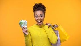 Signora nera allegra che tiene mazzo di euro e di sacchetti della spesa, vendita di festa fotografia stock libera da diritti