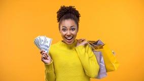 Signora nera emozionale che tiene mazzo di dollari e di sacchetti della spesa, contanti indietro immagini stock libere da diritti