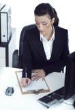 Signora occupata di affari che fa le sue note Immagini Stock Libere da Diritti