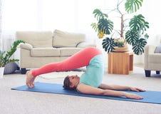 signora Ood di aspetto in asana dell'aratro sulla stuoia di yoga Fotografia Stock Libera da Diritti
