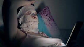 Signora osservata blu si trova e ripara la maschera dello strato nell'oscurità stock footage