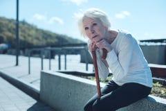 Signora pensionata nostalgico che si appoggia canna e sogno Fotografia Stock