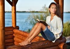 Signora Pensive con il libro nel summerhouse Immagini Stock Libere da Diritti