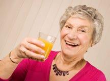 Signora più anziana maggiore con vetro del succo di arancia Fotografia Stock