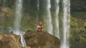 Signora Reads Diary su roccia fra le correnti della cascata archivi video