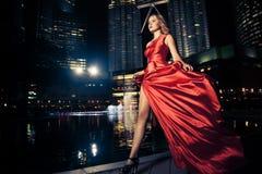 Signora In Red Dress di modo ed indicatori luminosi della città Immagini Stock