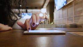 Signora riccia irriconoscibile in un ristorante sta lavorando online sul telefono stock footage