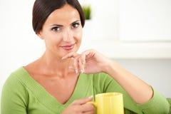 Signora rilassata che tiene una tazza gialla Fotografia Stock