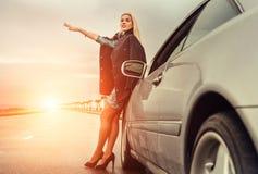 Signora in scarpe del tacco alto con l'automobile broked sulla strada principale Immagine Stock
